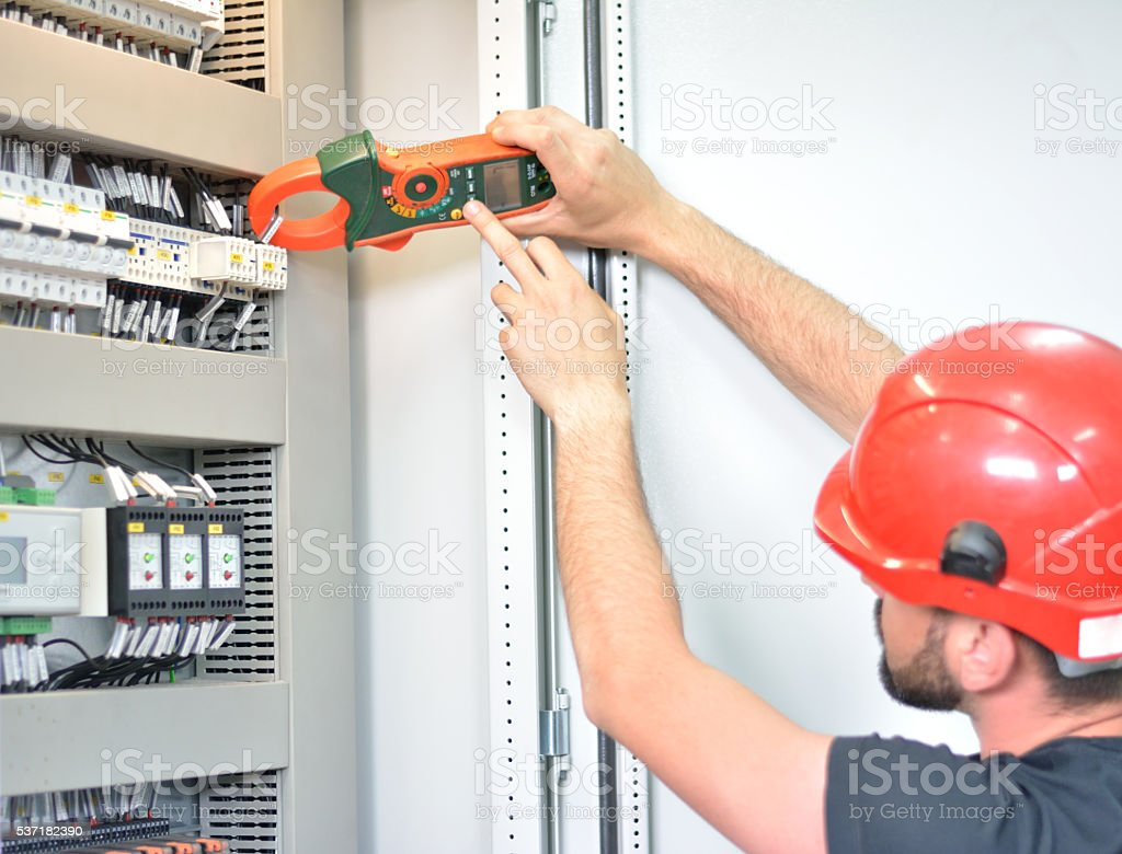 Electrician Testing Voltage with Clamp Meter stock photo