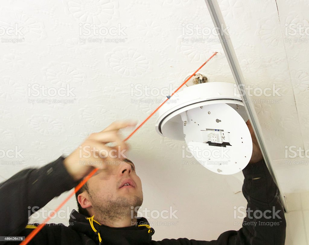 Electrician uses probe to search for a route for cables stock photo
