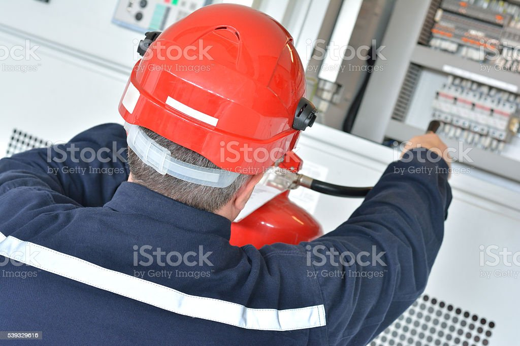 Electrician Using Fire Extinguisher in Utility Room stock photo
