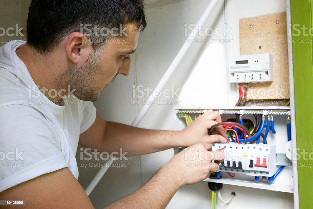 Electrician wiring a new circuit breaker for a residential property stock photo