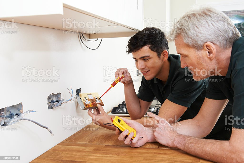 Electrician With Apprentice Working In New Home stock photo