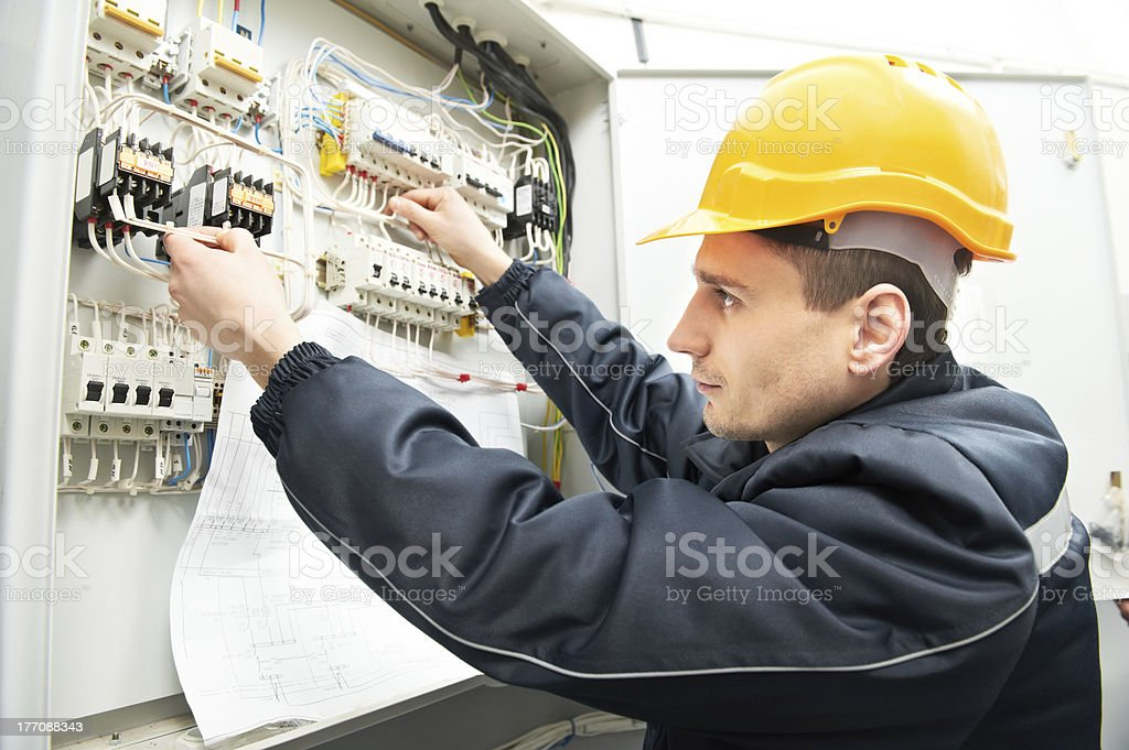 Electrician with drawing at power line box stock photo