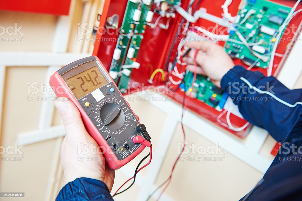 electrician work with multimeter tester stock photo