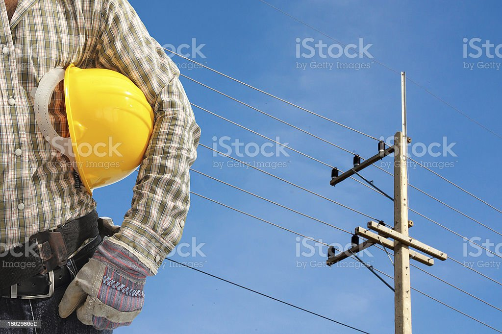 Electrician worker at work against electric post and blue sky royalty-free stock photo