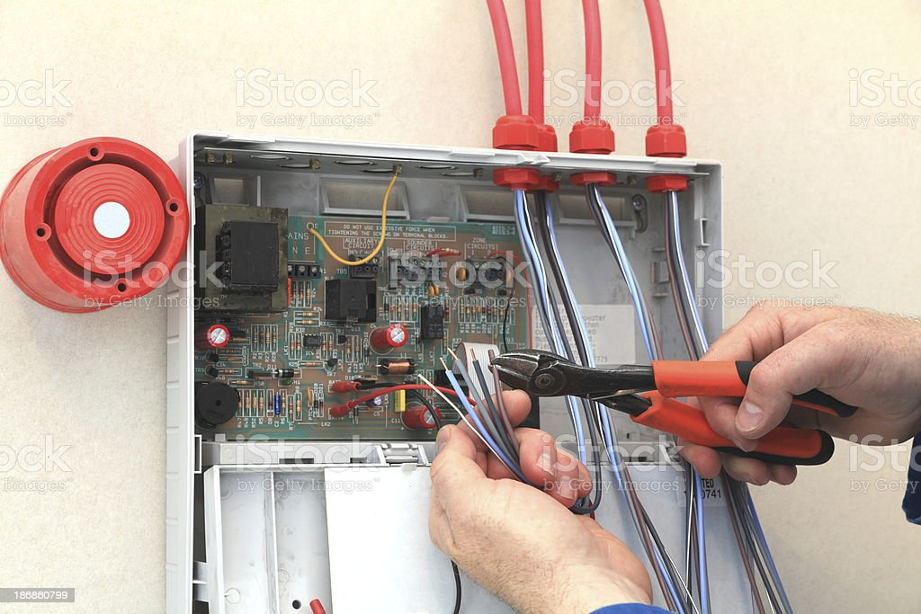 Electrician working at a Fire Alarm control box. stock photo