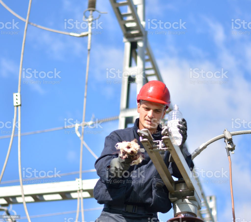 Electrician working at the height of the electricity substation stock photo