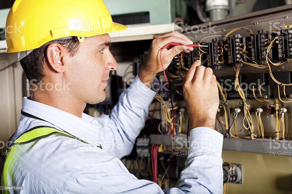 electrician testing industrial machine stock photo
