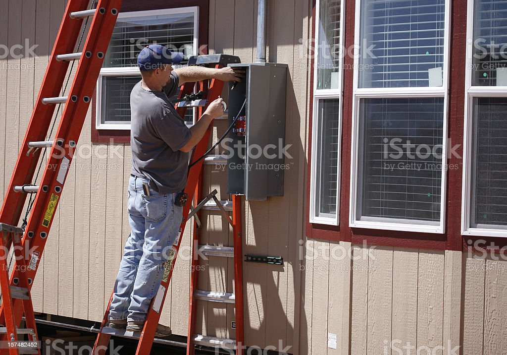 Electrician Working on Electrical Service Panel stock photo