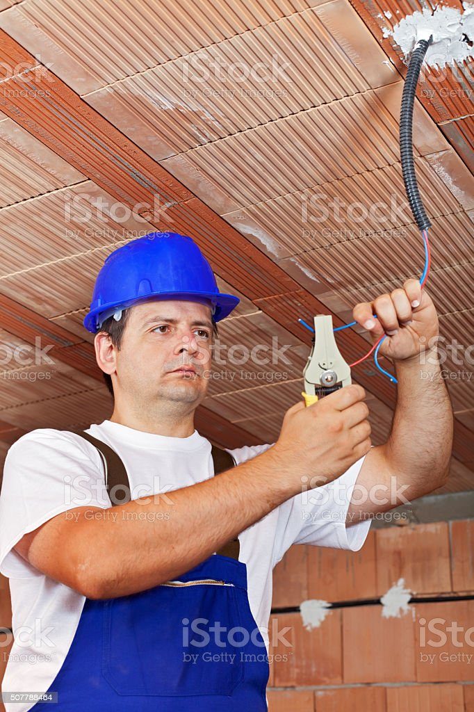 Electrician working with wiring in a new building stock photo