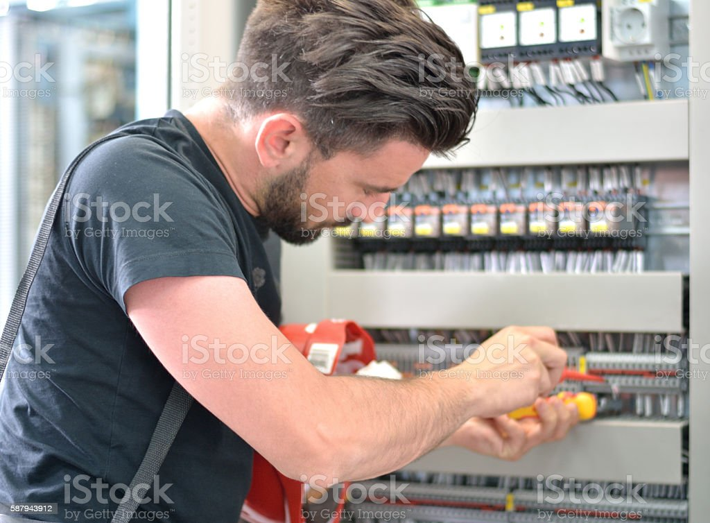 Electrician Working with Work Tool in Electric Room stock photo