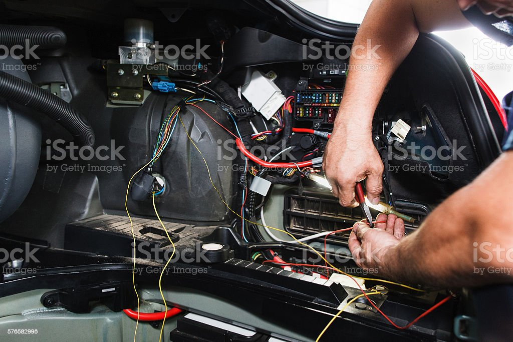 Electrician works with electric block in car stock photo