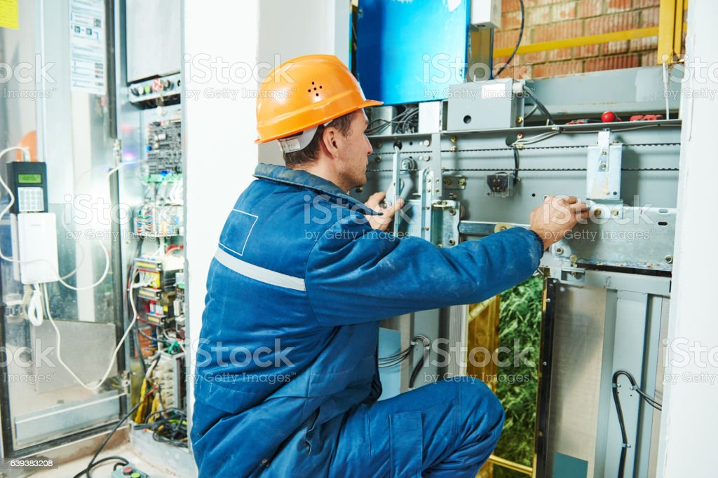 Electrician works with elevator lift equipment stock photo