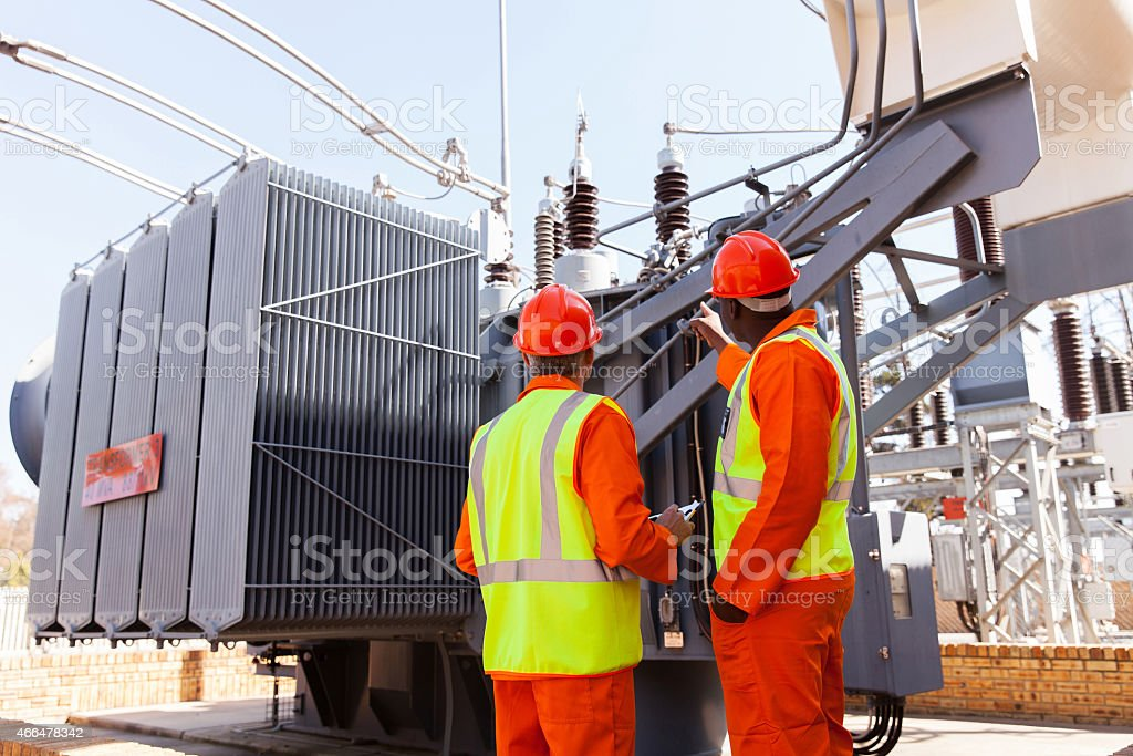 electricians standing next to a transformer stock photo