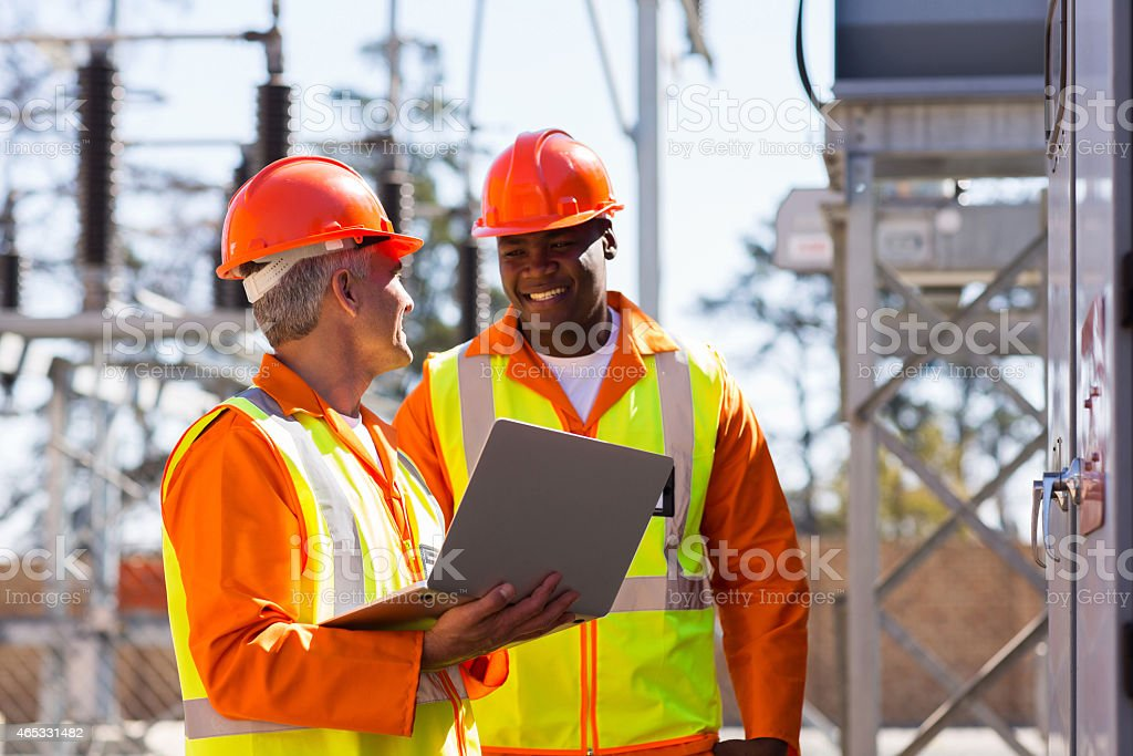 electricians using laptop computer in substation stock photo