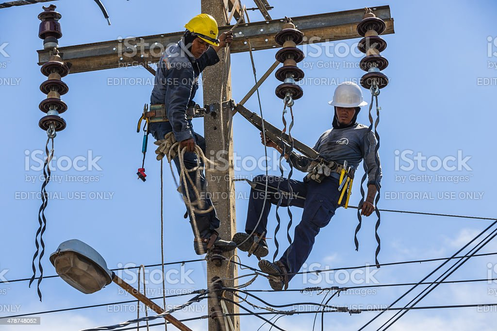 Electricians working together on the electricity pole stock photo