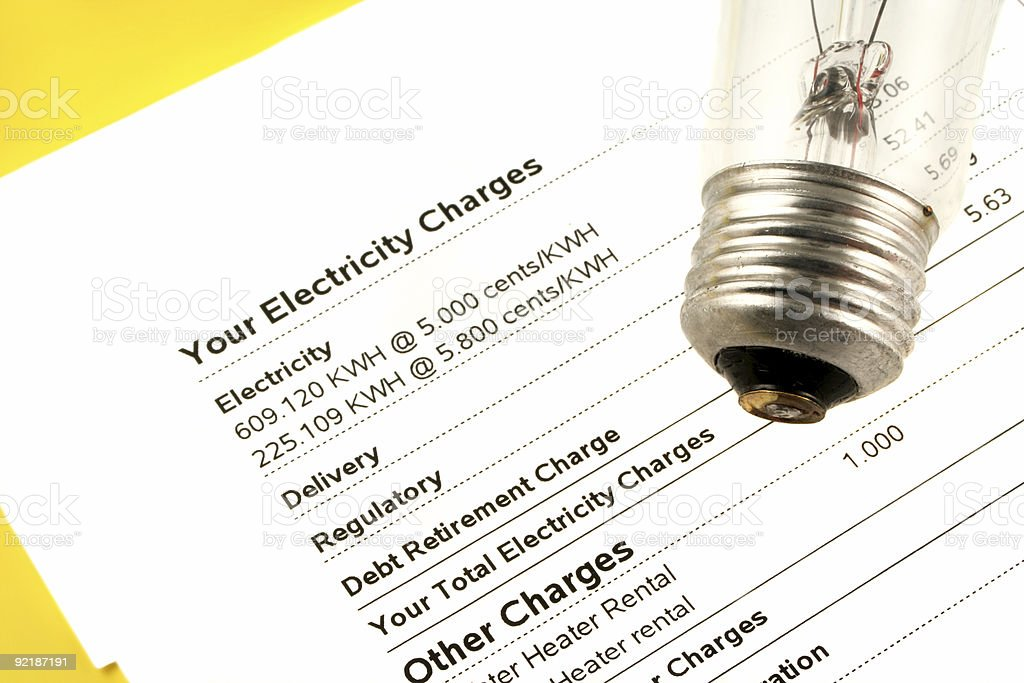 Electricity bill on a yellow table with a light bulb stock photo