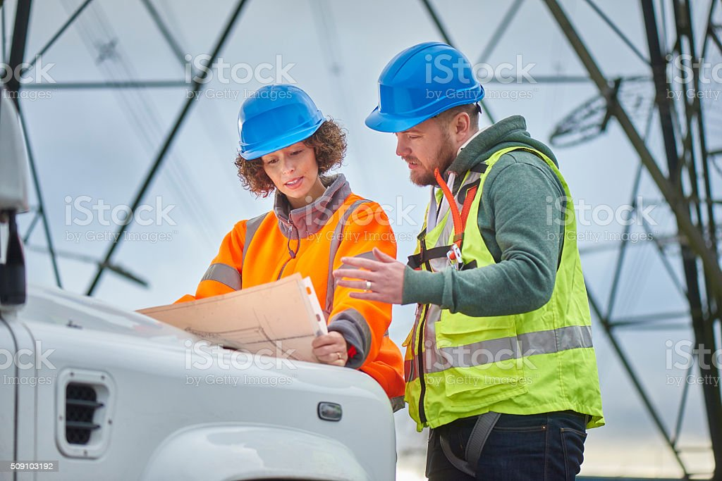 electricity engineers and contractor beneath an electricity pylon stock photo