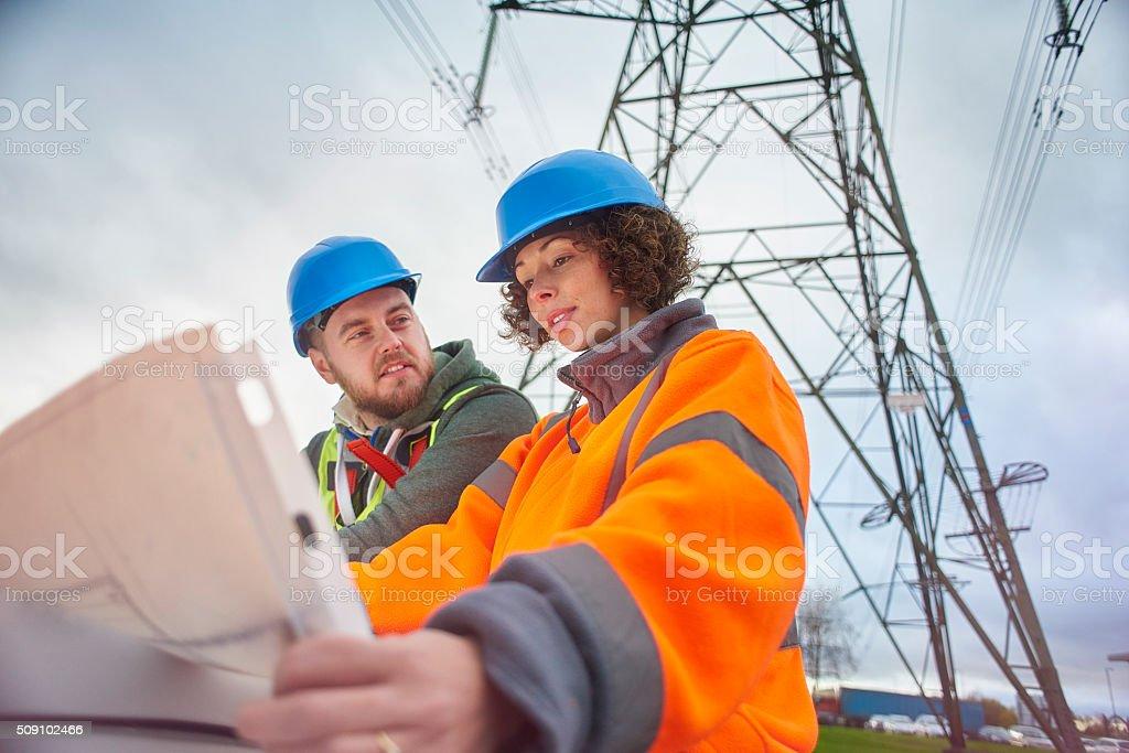 electricity engineers beneath a pylon stock photo