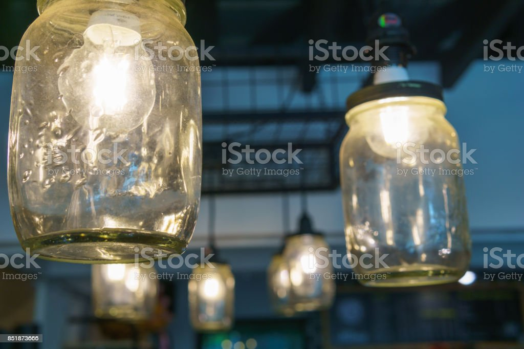 electricity light bulb glowing in the transparent vase hanging on the ceiling for abstract background or special occasion background. stock photo