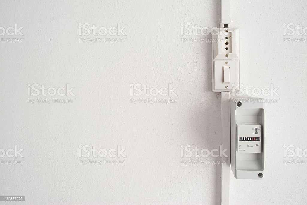 electricity meter in a white wall stock photo