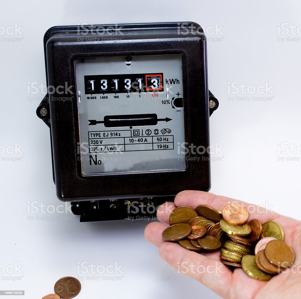 electricity meter with the hand full of European currencies stock photo