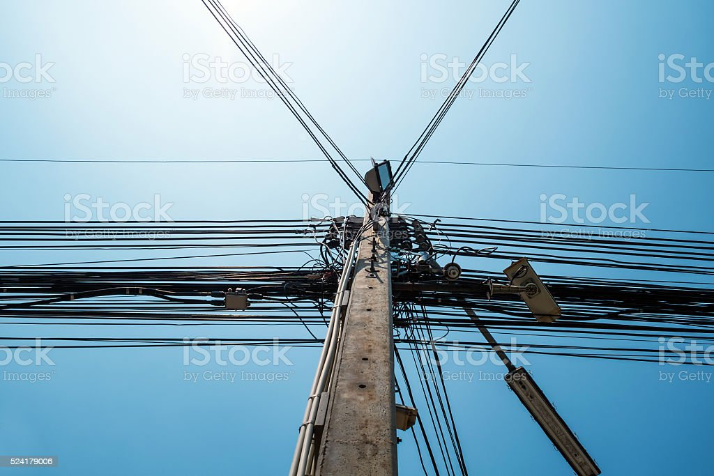 Electricity pole with messy electrical cables and street light stock photo