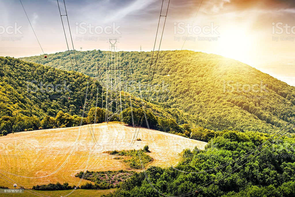 Electricity power line high voltage pylon hill landscape at sunset stock photo