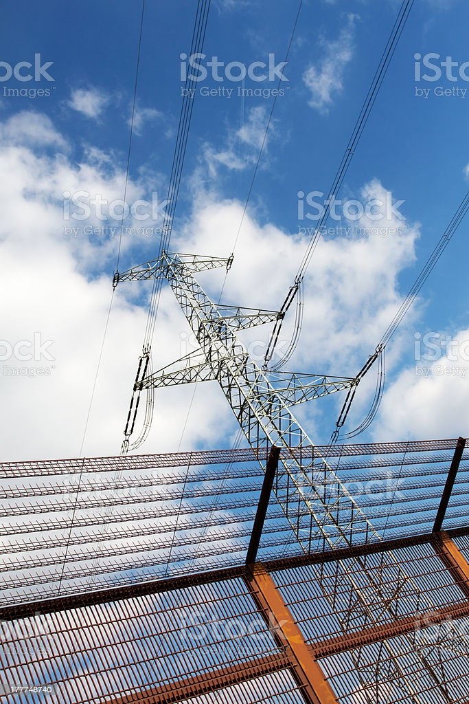 Electricity pylon and barrier fence against the blue sky royalty-free stock photo