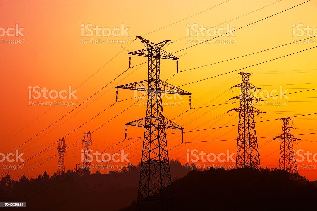 Electricity pylon at sunrise stock photo
