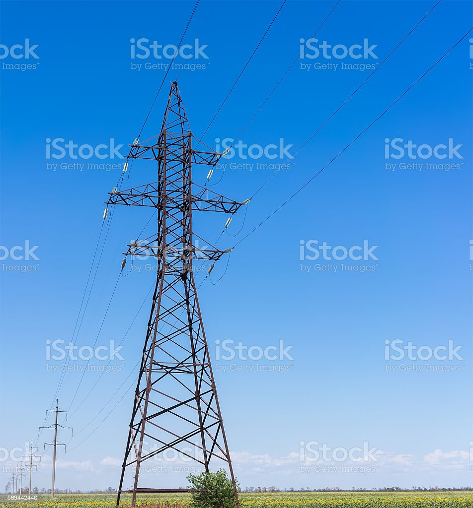 Electricity pylon silhouette against blue sky background. High voltage tower stock photo