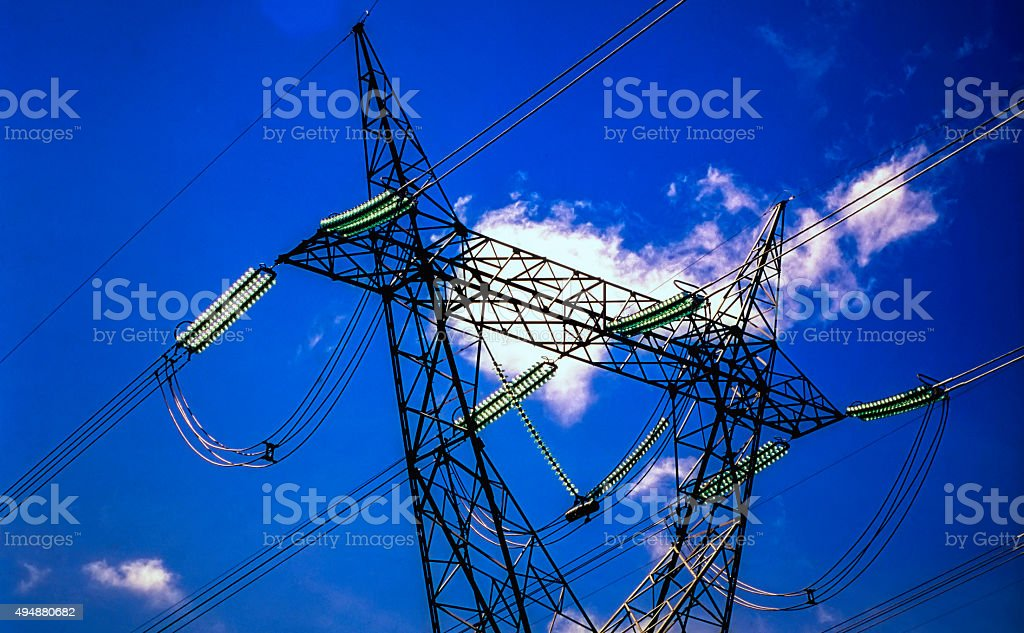 Electricity pylon with blue sky and sun stock photo