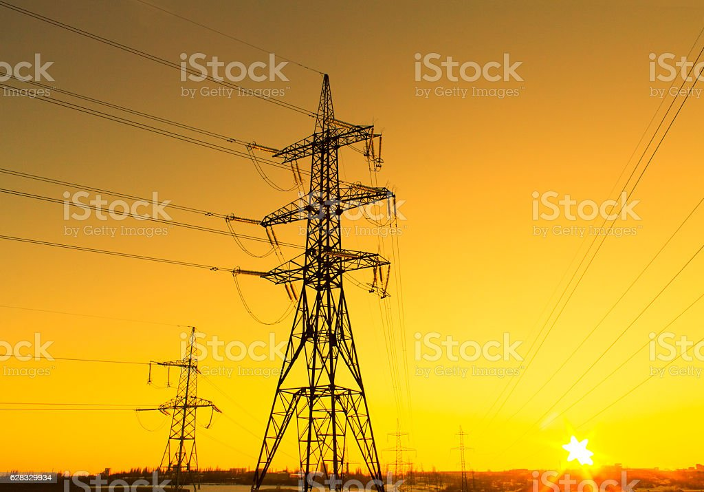 Electricity pylons and lines beautiful sky and the sunset over the...