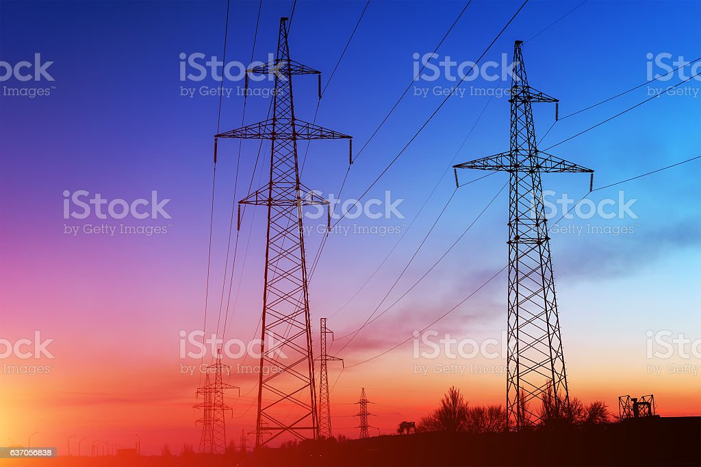Electricity pylons and lines at dusk at sunset. stock photo