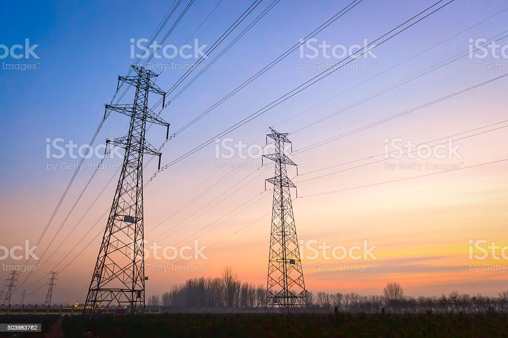 Electricity pylons and lines at dusk. stock photo