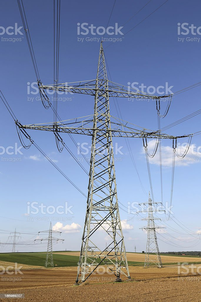 Electricity pylons and lines on a field royalty-free stock photo
