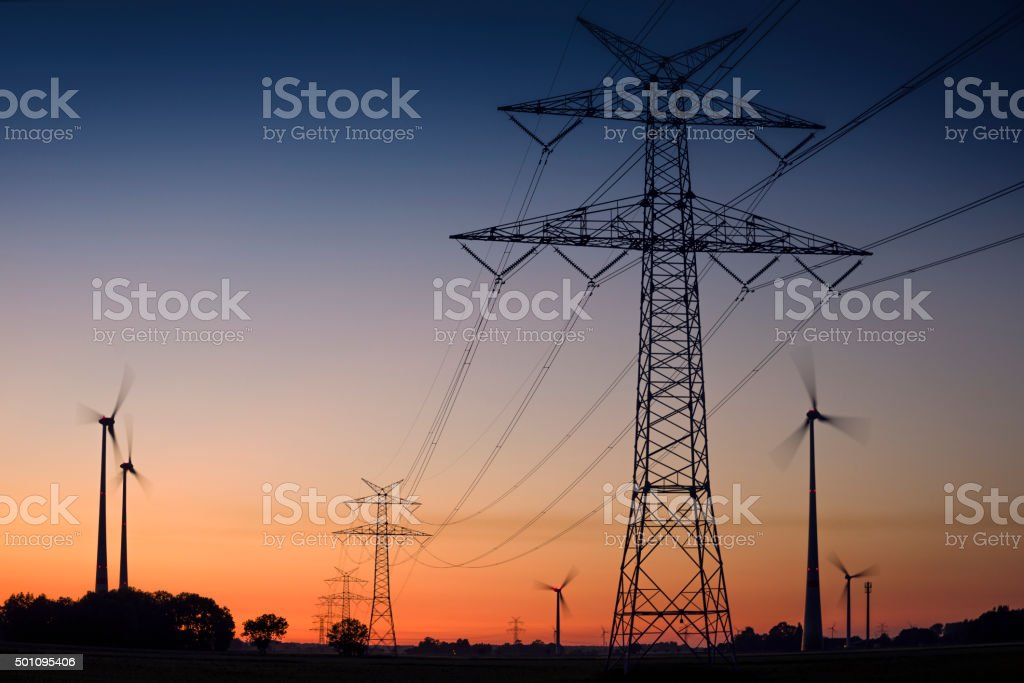 Electricity pylons and wind turbines at dusk stock photo