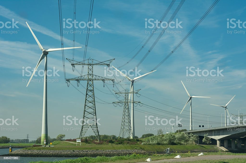 Electricity pylons and wind turbines in Rotterdam harbor area stock photo