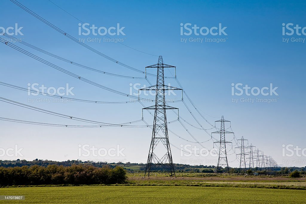 Electricity Pylons crossing along a green field stock photo