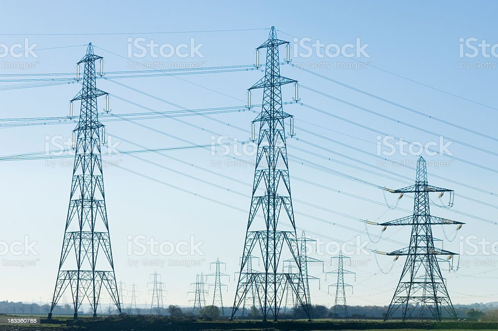 Electricity pylons in the distance under a clear blue sky royalty-free stock photo