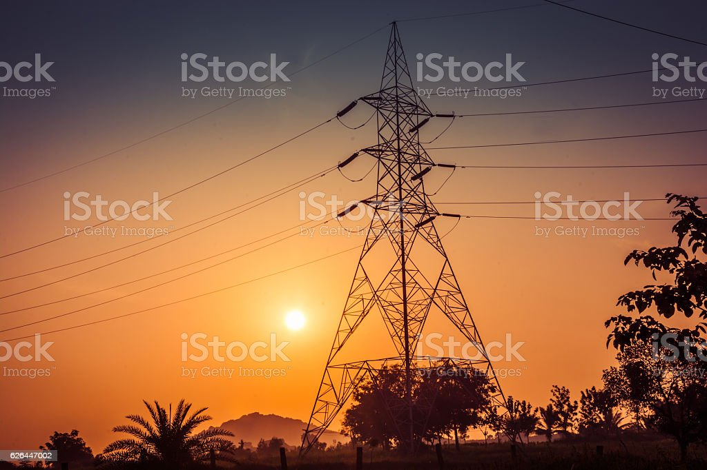 Electricity pylons, power lines at sunset stock photo