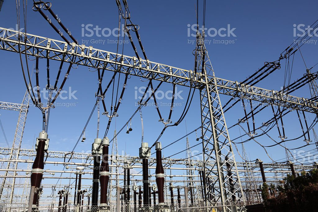 Electricity substation against clear blue sky stock photo