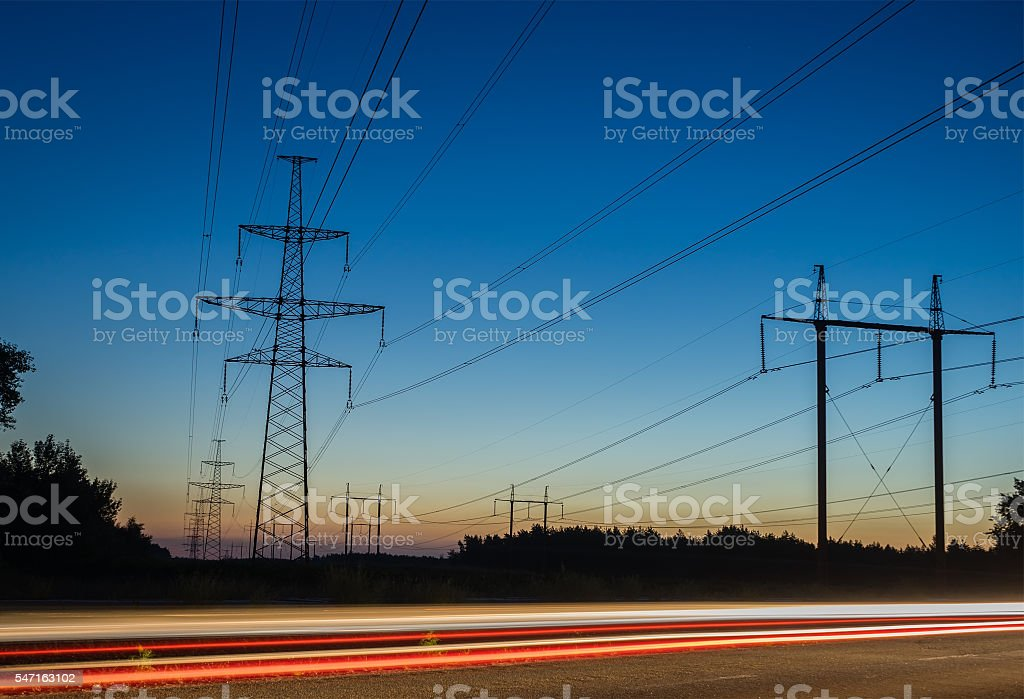 Electricity transmission power lines at sunset High voltage tower. stock photo
