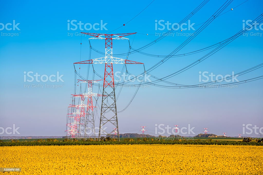Electricity transmission pylon silhouetted against blue stock photo