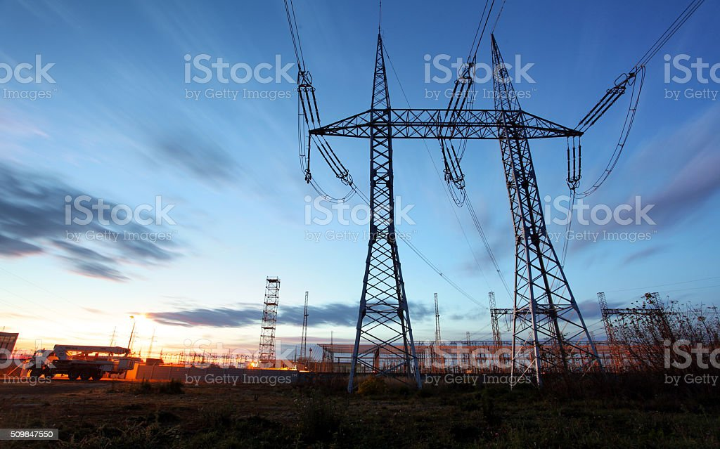 electricity transmission pylon silhouetted against blue sky at dusk stock photo