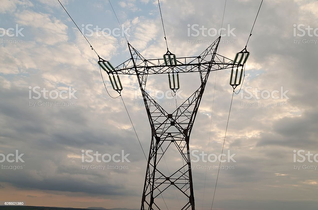 Electricity transmission pylon silhouetted against blue sky stock photo