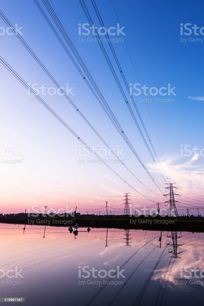 Electricity voltage transmission tower by the lake in sunset. stock photo