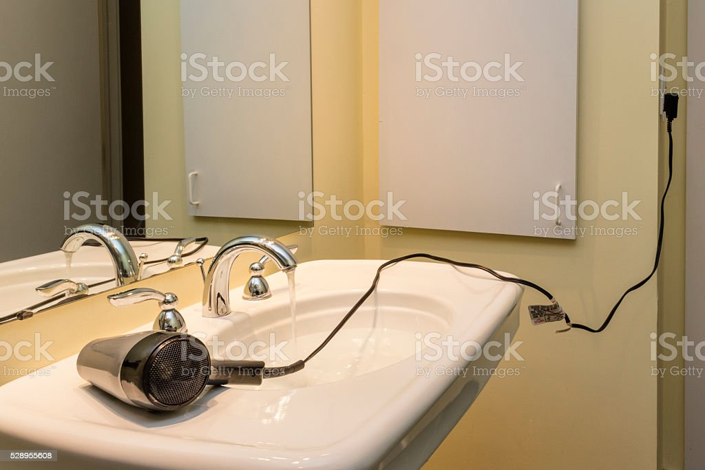 Electrocution risk from hair dryer near sink stock photo