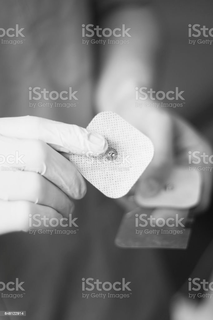 Electrode stimulation electro physiotherapy electrodes in medical center in hands of physiotherapist. stock photo