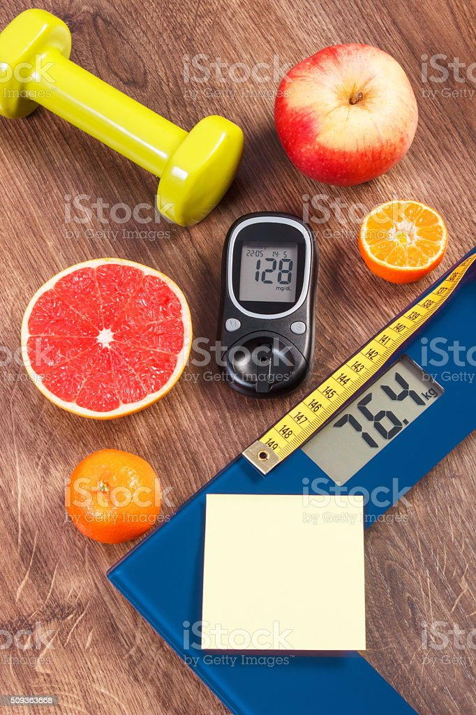 Electronic bathroom scale and glucometer, centimeter, healthy food and dumbbells stock photo
