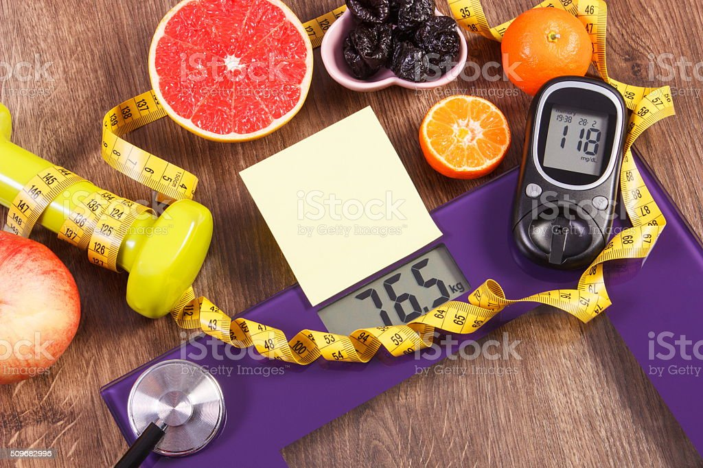 Electronic bathroom scale and glucometer, healthy food and dumbbells stock photo